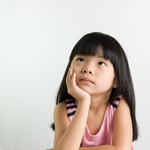 Little Asian girl child thinking over white background